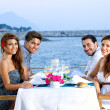 Two happy couples having dinner at the seaside — Stock Photo