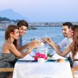 Friends celebrating at a seaside restaurant — Stock Photo