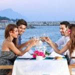 Friends celebrating at a seaside restaurant — Stock Photo
