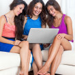 Three young barefoot girlfriends sitting on sofa with laptop, la — Stock Photo