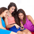 Foto Stock: Three beautiful young female friends looking at cell phone.