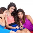 Three beautiful young girlfriends having fun with smart cell pho — Stock Photo
