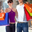 Cheerful young couple with colorful shopping bags — Stock Photo