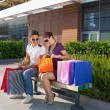 Happy young couple sitting on a bench in front of a shopping mall with colorful shopping bags, relaxing — Foto Stock