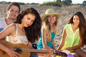 Couple and two female friends sitting on the beach playing guita — Stock Photo