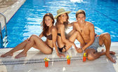 Friends sunbathing at the edge of a pool — Stock Photo