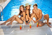 Amici godendo drink a bordo piscina — Foto Stock