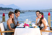 Couples celebrating at a seaside restaurant — Stock Photo