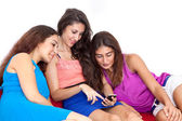 Three beautiful young female friends looking at cell phone. — Stock Photo