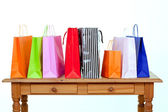 Colorful shopping bags on table — Stock Photo