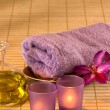 Essential oil, candles, towel and purple flowers. — Stock Photo #32596719