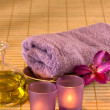 Stock Photo: Essential oil, candles, towel and purple flowers.