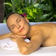 Woman with eyes closed, lying on a spa bed. — Stock Photo