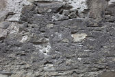 Old plastered stonewall, dark grey. — Stock Photo