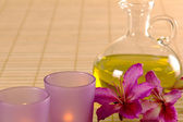 Essential oil, candles and purple flowers. — Stock Photo