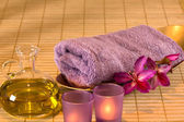 Essential oil, candles, towel and purple flowers. — Stock Photo