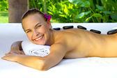 Woman in a prone position, with massage stones. — Stock Photo