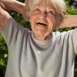 Senior lady enjoying the sunshine outdoors in her garden — Stock Photo #34294493