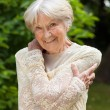 Senior woman holding her arms around herself in a park — Stock Photo