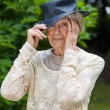 Senior woman putting on her hat smoothing down her hair under the brim — Stock Photo