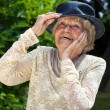 Elderly lady wearing a hat in a summer garden — Stock Photo