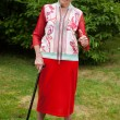 Elderly woman standing with her walking stick — Stock Photo