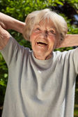 Senior lady enjoying the sunshine outdoors in her garden — Stock Photo