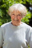 Grey haired senior woman in the garden — Stock Photo