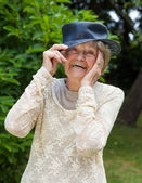 Laughing elderly lady wearing a hat in park — Stock Photo