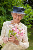 Lady holding a bunch of fresh pink lilies — Stock Photo