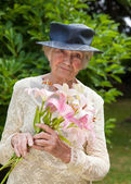 Senior lady holding a bouquet of fresh lilies — Stock Photo