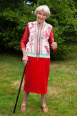 Senior woman in an elegant red outfit in her garden — Stock Photo