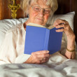Elderly woman reading a book in bed — Stock Photo