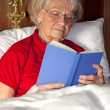 Senior woman reading a book in bed — Stock Photo