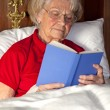 Senior woman reading a book in bed — Stock Photo #34302793