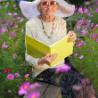 Elegant elderly lady reading in the garden — Stock Photo