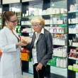 Pharmacist helping a senior lady — Stock Photo