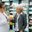 Pharmacist helping a grateful senior patient woman — Stock Photo