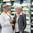 Pharmacist assisting an elderly lady — Stock Photo
