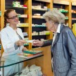 Smiling pharmacist serving a senior lady — Stock Photo