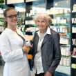 Senior lady shaking hands with a young female pharmacist — Stock Photo