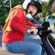 Senior woman riding her scooter — Stockfoto