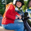 Laughing active senior woman on a scooter — Stock Photo