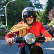 Senior lady riding a scooter. — Stock Photo