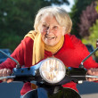 Senior woman speeding on a scooter bike — Stock Photo