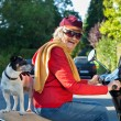 Laughing senior woman riding a scooter with her dog — Stock fotografie