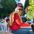 Laughing senior woman riding a scooter with her dog — Stock Photo