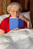 Elderly woman reading in bed — Stock Photo