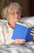 Elderly woman reading a book in bed — Stockfoto