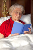 Senior woman reading a book in bed — Stockfoto